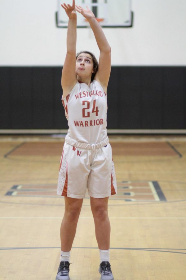 Following through, Ella Wood '23 watches the ball as it goes towards the net. This was the first of two free throws.
