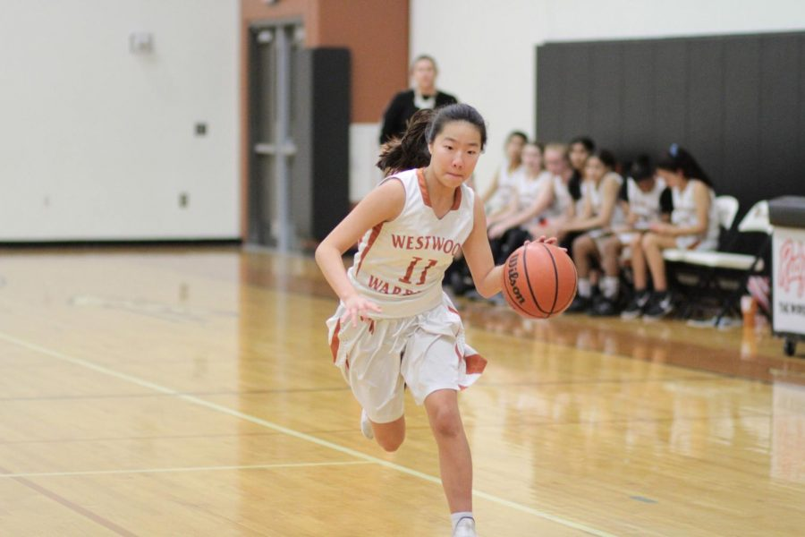 Bringing the ball up the court, Olivia Yang '23 focuses on dribbling the ball. Name set up a drill that scored the Warriors another two points.