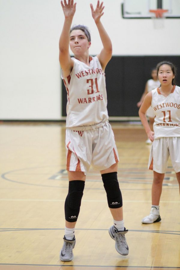Kylie Wardlow '23 reaches up to shoot the ball for a free throw. The free throws earned the Warriors two more points.
