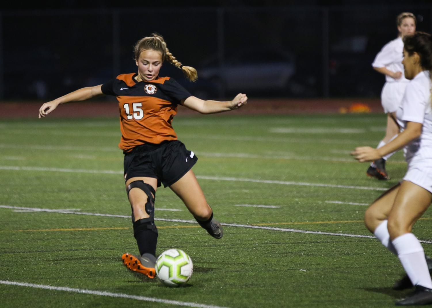 Leaning+back%2C+Cate+Defendorf+%2723+kicks+the+ball+further+down+the+field.+Defendorf+plays+midfield+so+she+helps+connect+the+offensive+and+defensive+lines.