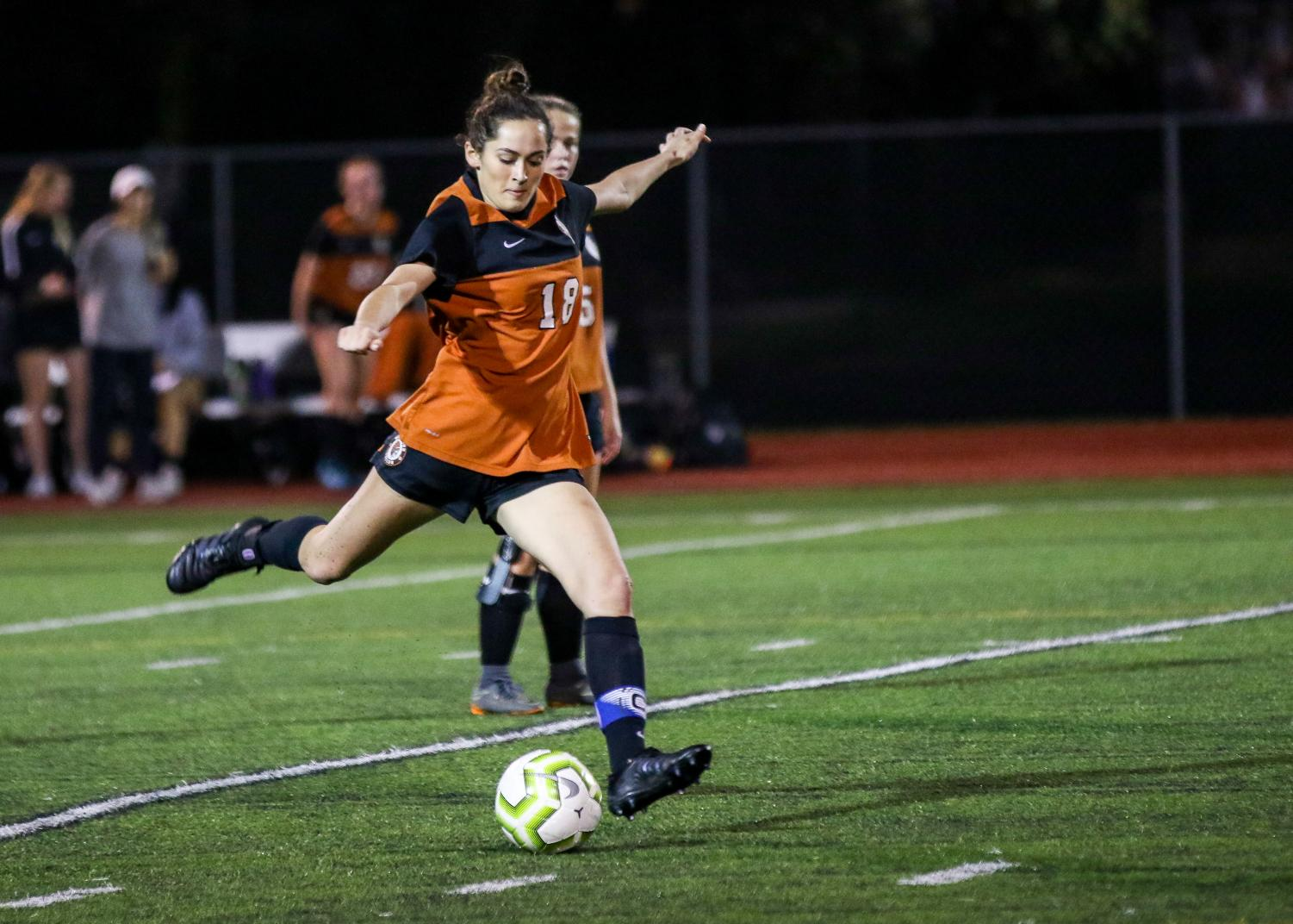 In+the+air%2C+Claire+Carpenter+%2721+kicks+the+ball+towards+the+goal.+Since+Carpenter+plays+middle%2Fforward%2C+she+focuses+more+on+scoring+and+dribbling+the+ball+well.+