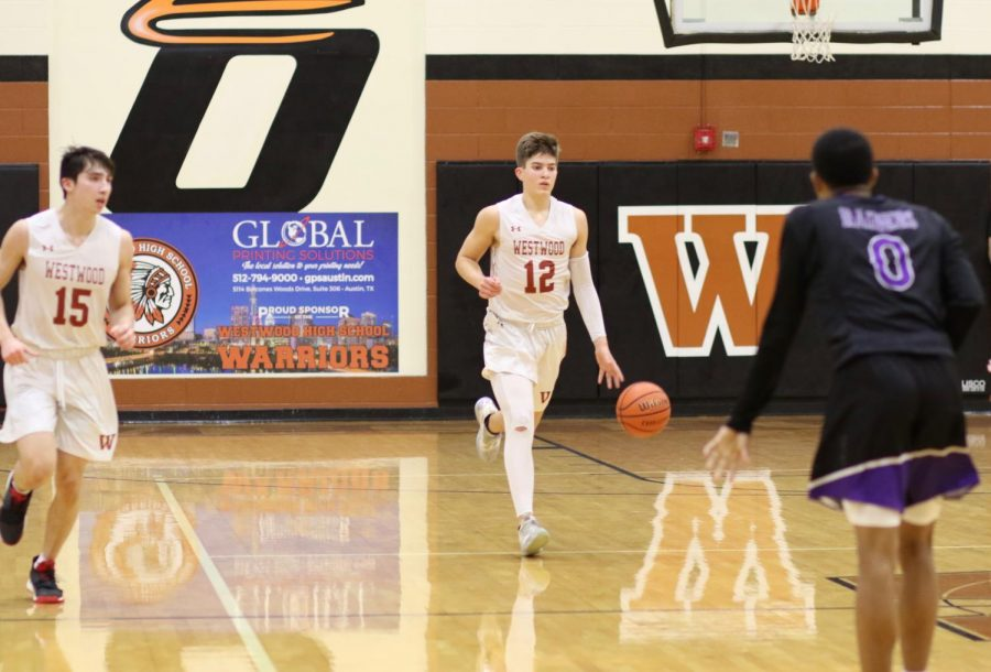 Taking the ball up the court, Zach Engels '22 looks to set up an offensive play. This play ended up scoring the Warriors two more points.
