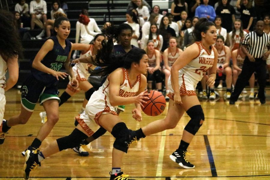 Annalise Galliguez '20 passionately dribbles the ball down court to try and score a basket for the Lady Warriors. She was able to score the very first score of the game, and despite the girls starting strong, they still lost 51-63.