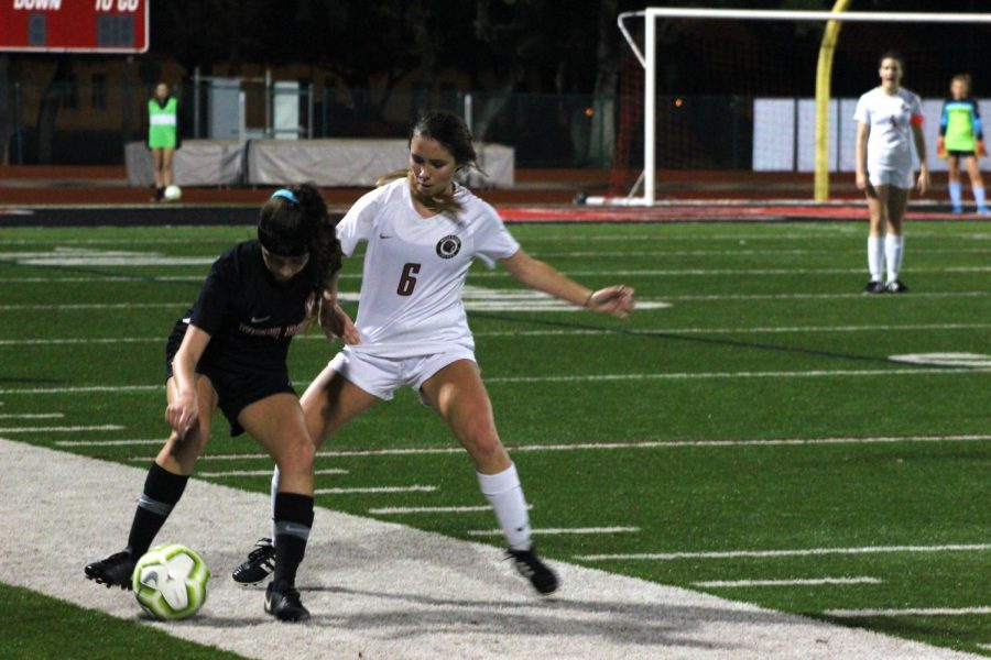 Aislinn Concannon '22 goes up against a Vista Ridge player to try and give the ball to the Lady Warriors. She was successfully able to get the ball and give it to her teammates.