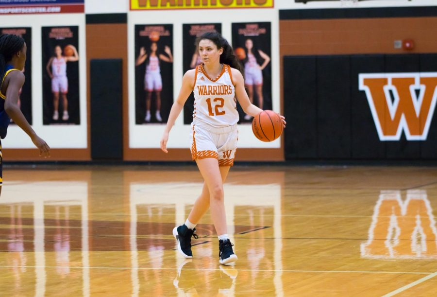 Dribbling the ball down the court, Desi Davalos '22 scans the court for an opening. Davalos would go on to make a three-pointer during the first quarter which brought the score to 10-2.