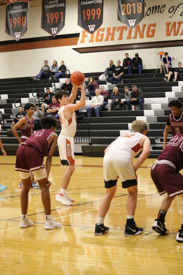 Getting ready to shoot a free throw, Carson Turner '22 lifts the ball in the air. He ended up making the shot, getting the Warriors a point.