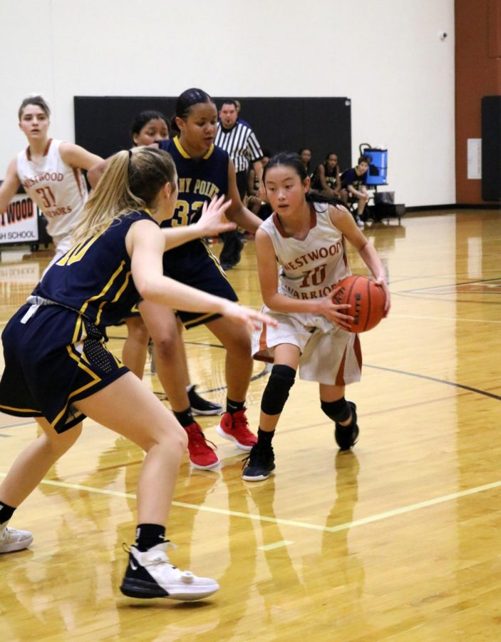 Navigating around the Tigers' defense, Olivia Yang '23 attempts to pass to her teammates. As point guard, Yang plays a critical role in games.