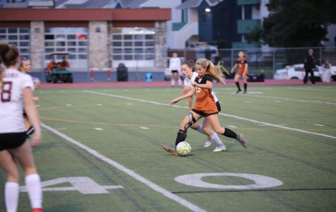 Defender Cate Defendorf '23 recovers the ball and dribbles it back to her teammates. Despite their efforts, the Lady Warriors were unable to score in the first half of the game.