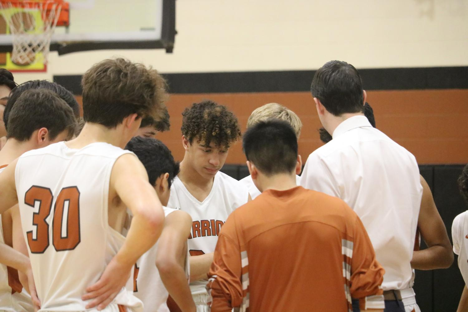 The+JV+boys+huddle+up+to+their+coach+in+the+first+quarter.+In+the+timeout%2C+the+boys+reflected+on+their+plays.