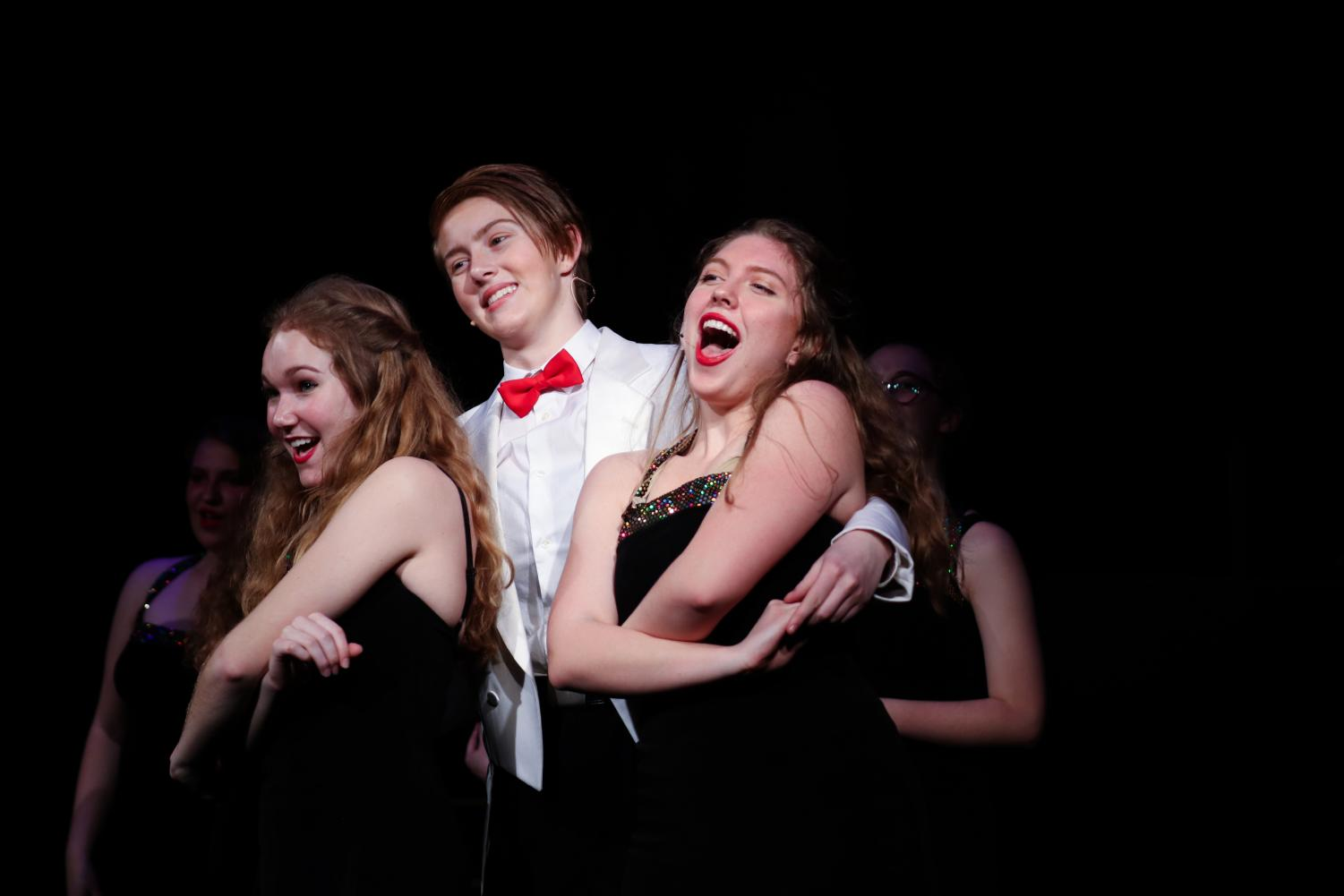 Laney+McFadden+%2720+sings+as+her+character+Billy+Flynn%2C+as+she+is+surrounded+by+members+of+the+ensemble.+