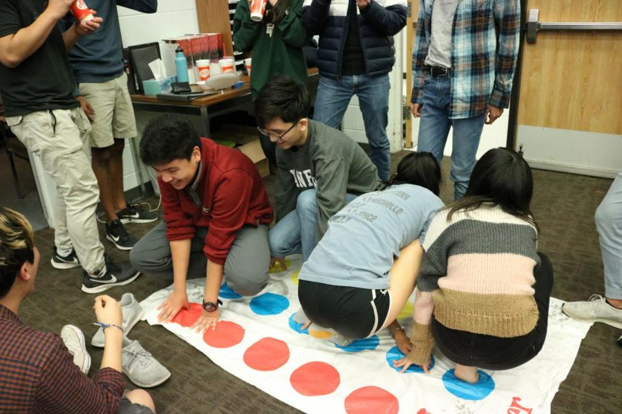 Orchestra students enjoy a game of Twister. There were multiple sets of Twister to play with.