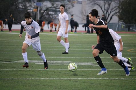 Joeb Goheen '22 and a Ranger race to gain possession the ball. Goheen ended up winning over the ball and passed it to a teammate.