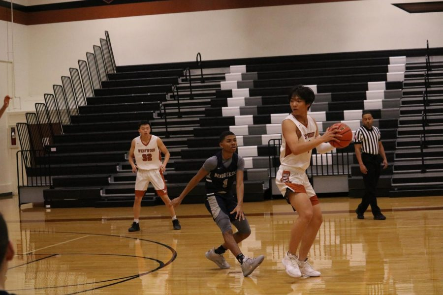 Keeping the ball away from the defenders, Josh Choy '22 attempts to make a shot. In the face of the Hawks' attempted comeback, Choy helped the Warriors triumph through earning consistent points.