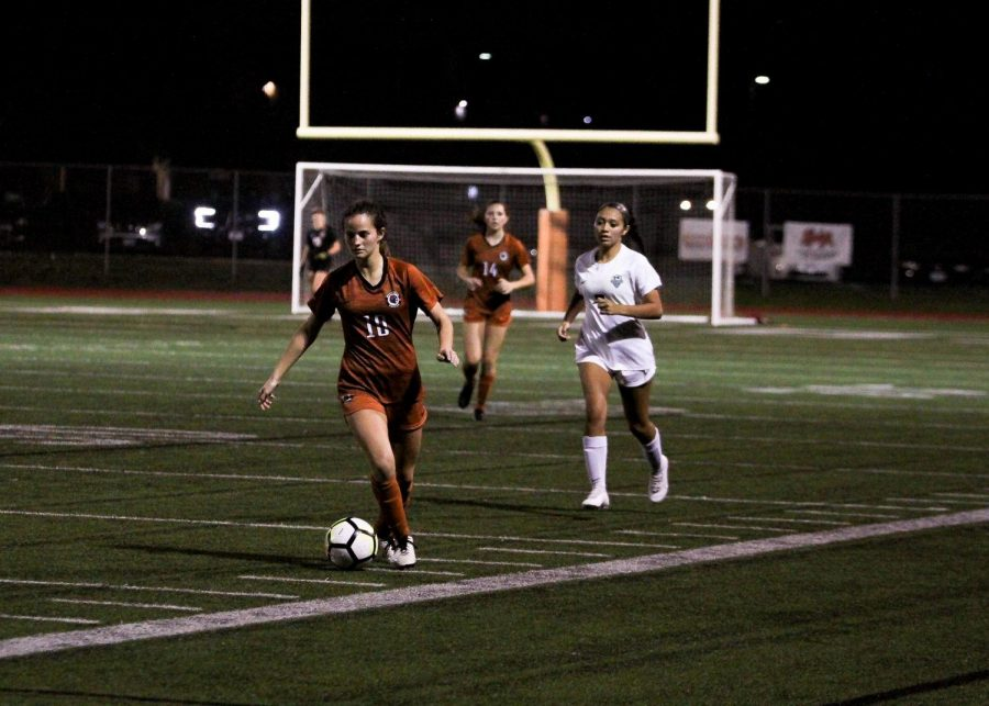 Hailey Martinez '21 dribbles the balls near the sidelines. Martinez is a midfielder for the team.