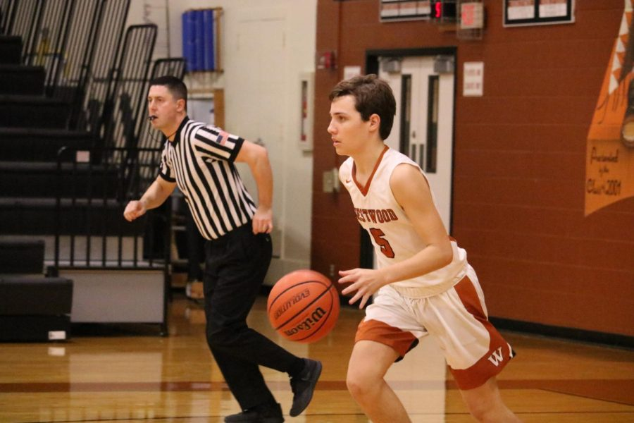 Dribbling the ball, Karsten Bresser '22 takes it up the court. Throughout the game, the Warriors constantly fought hard to keep the Hawks from gaining a lead.