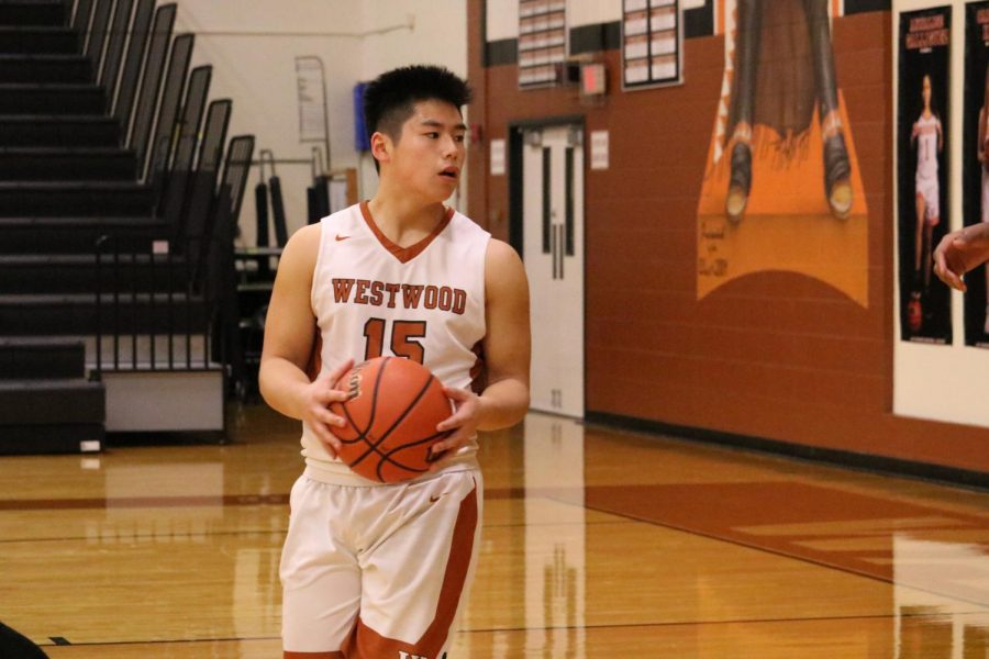While watching out for the opposition, Robbie Jeng '21 dribbles the ball in the first quarter. The game started off slowly with the Warriors trailing by four points.