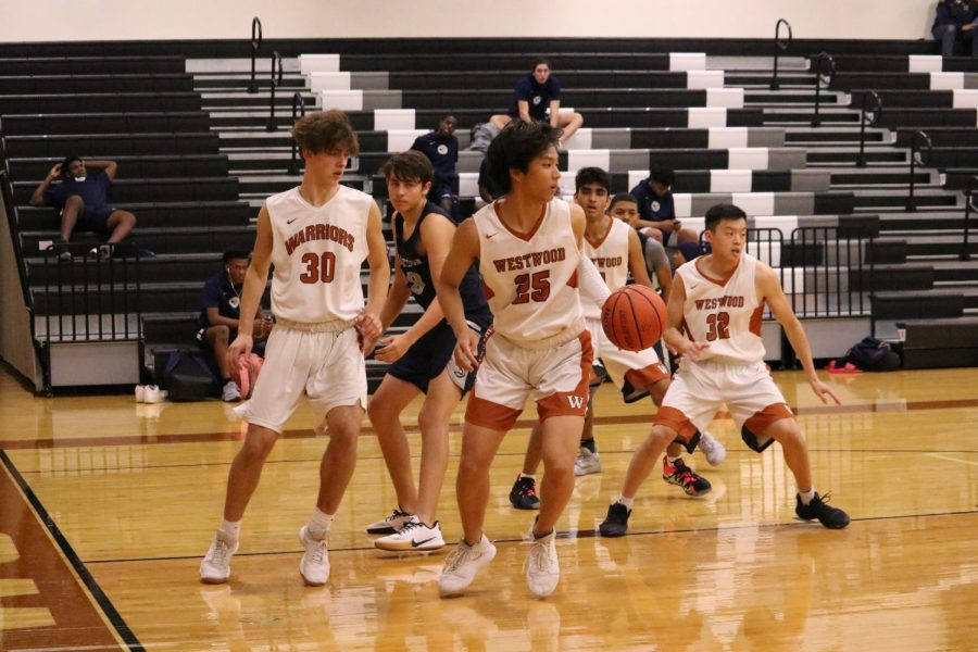 Josh Choy '22 looks up the court as he keeps the ball from the Hawks. After making a shot for the Warriors, Choy passed the ball to one of his teammates in the next Warriors possession.