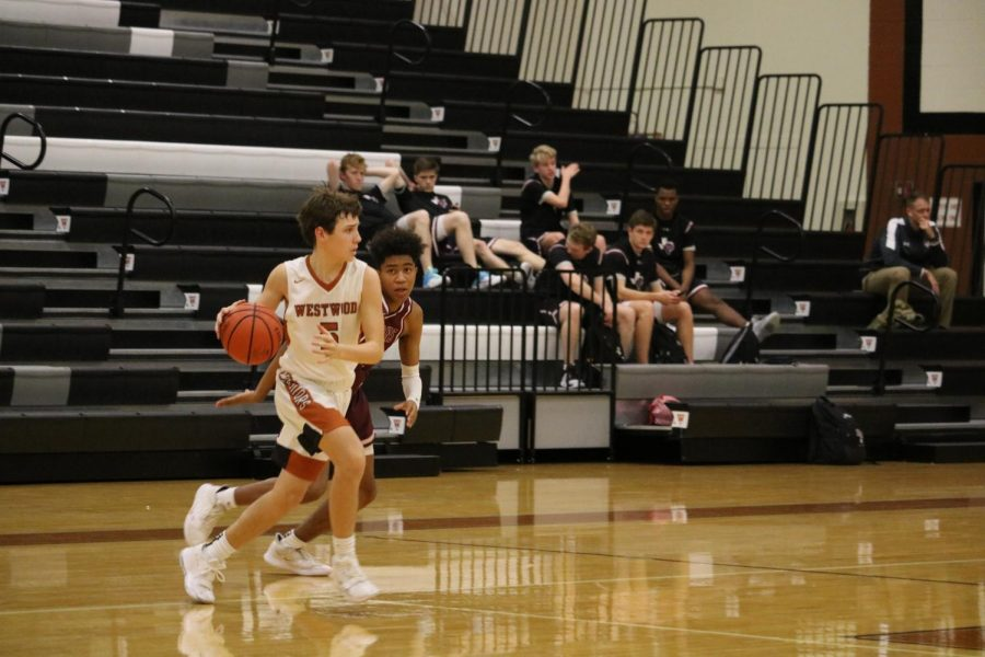 Turning to avoid a Dragon player, Karsten Bresser '22 dribbles his way down the court. With a coordinated effort, the Warriors were able to make a basket.