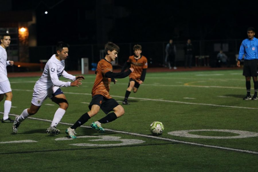 Tom Gentot '20 dribbles the ball upfield with an opponent close behind. Gentot passed the ball to teammate Cesar Frias '20.