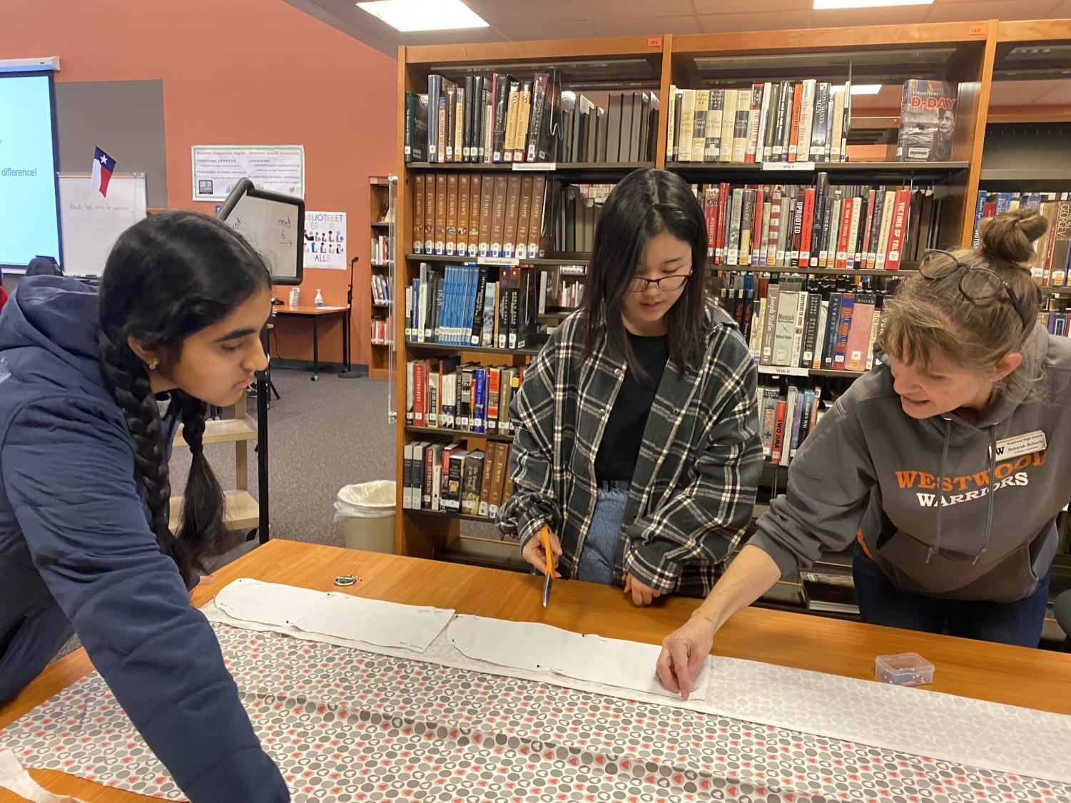 Librarian+Ms.+Deborah+Roberts+shows+students+how+to+measure+and+cut+the+fabric+at+the+beginning+of+the+session.