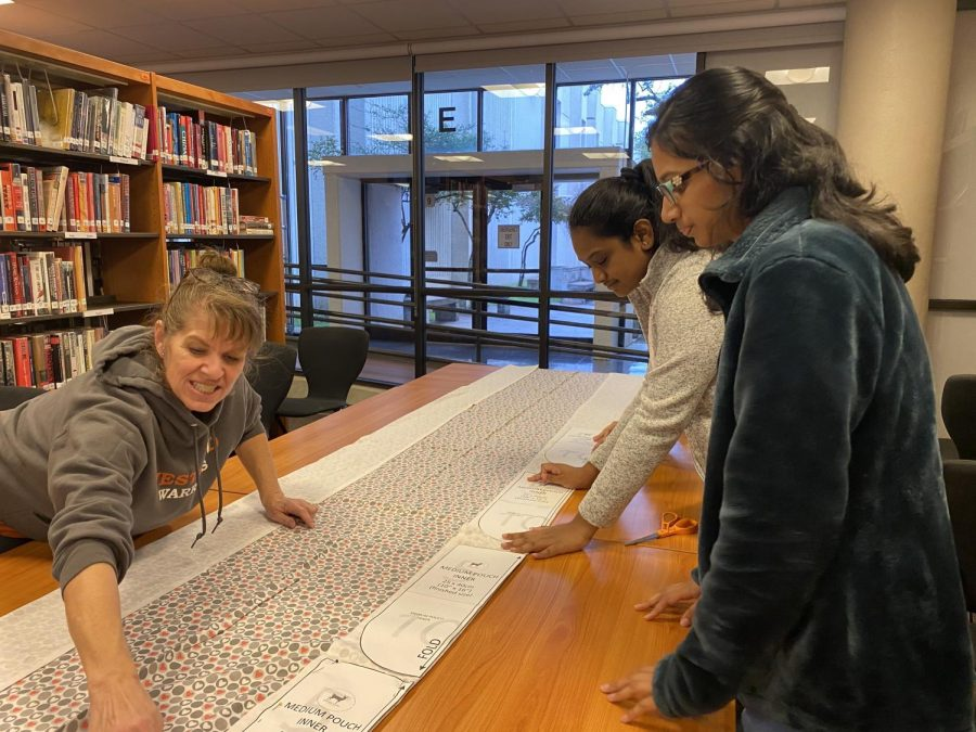 Juniors Nivrithi Kuttuva and Srimayee Gadde watch as librarian Ms. Deborah Roberts explains how to pin the fabric with the measuring paper and cut it.