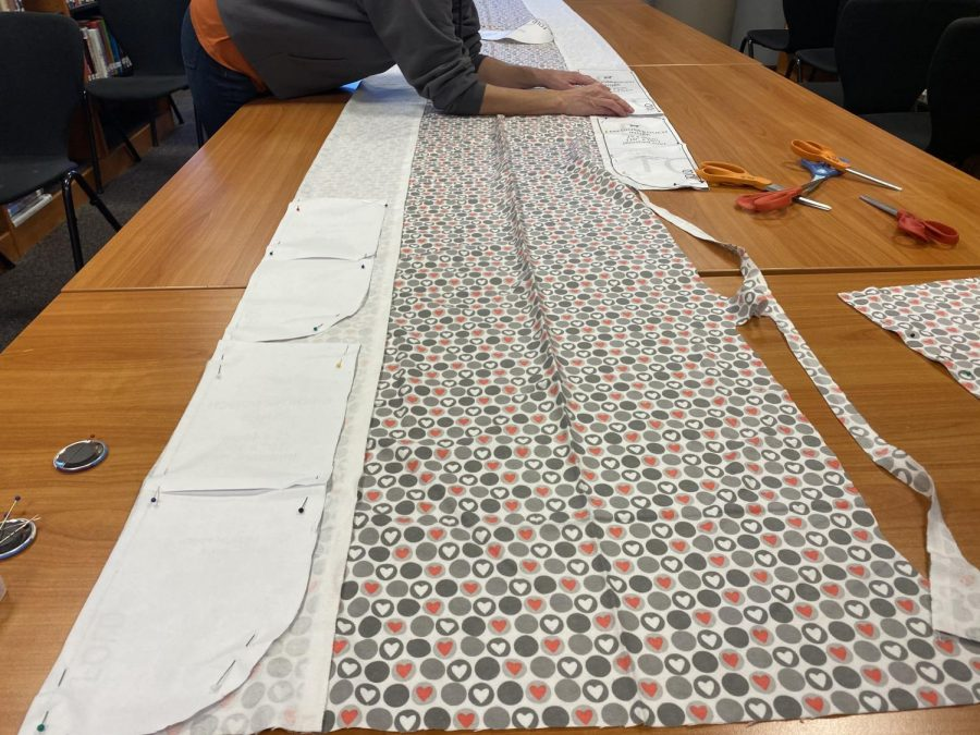 The fabric is spread out on tables across the Great Room in the library, ready for students to cut and pin for the pouches.