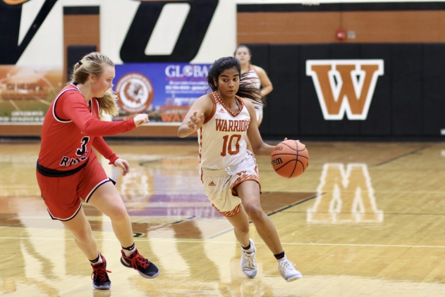 Blocking the defender, Anisha Chintala '21 heads to the basket. Chintala ended up getting to the basket and scored a layup for the team.