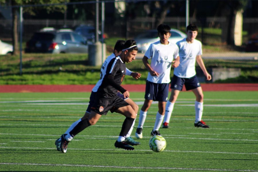 Rushing against an enemy maverick Emmanuel Molina '23 goes after the ball to gain control over it for the warriors. He was able to beat the Mcneil player and give the warriors an advantage.