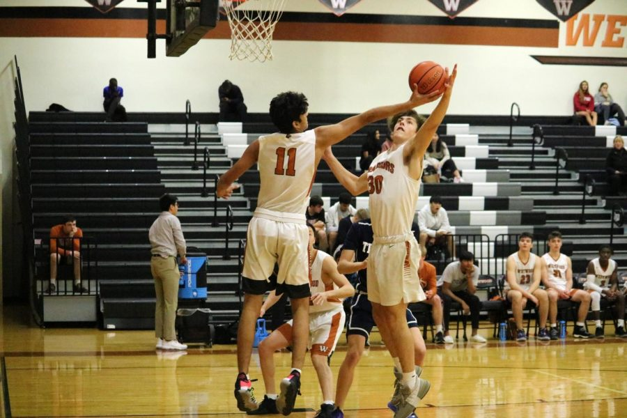 Power forward Josef Borkowski '21 and small forward Vinay Majjiga '22 both leap into the air in hopes of rebounding the ball. Majjiga was able to successfully get the ball putting it back in the Warriors' control.