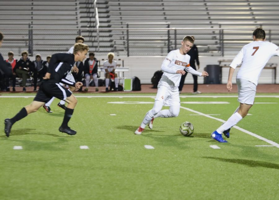 With a defender right behind him, Philip Richardson '20 passes the ball to a teammate. This is Richardson's last season on the varsity team because he's graduating in the spring.