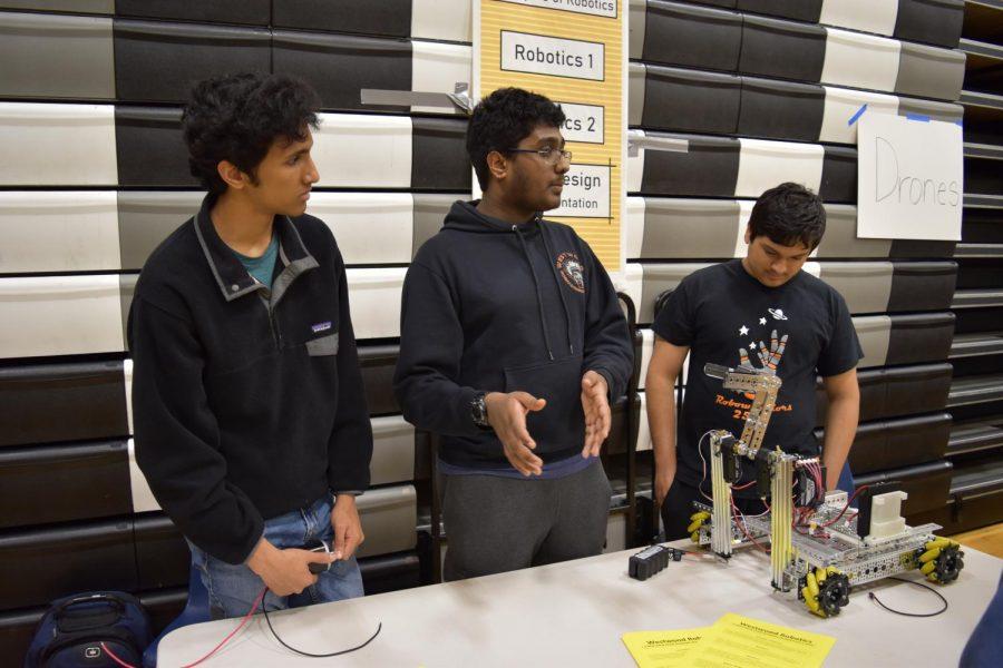 Shreyes Kaliyur '20, Rohan Polavaram '21, and Rohan Dange '21 show off a robot to introduce the robotics courses. A poster at the booth displayed the robotics course path, beginning with the freshman Principles of Robotics class.