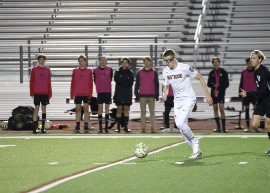 Looking down, Louis Neimerg '21 dribbles the ball up the field. Despite their efforts, the Warriors unfortunately didn't win the game.