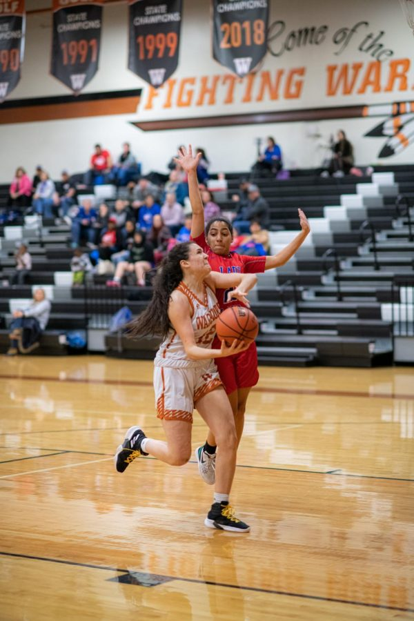 Power forward Desi Davalos '22 shoots a lay up. Davalos was successfully able to make the shot, earning more points for the Lady Warriors.