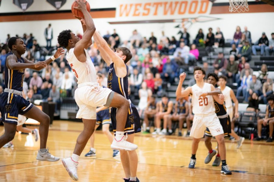 Brandon Parks '20 jumps to pass the ball to a teammate over the blocking defender. The play ended in a foul on Westwood giving Parks two free throws.