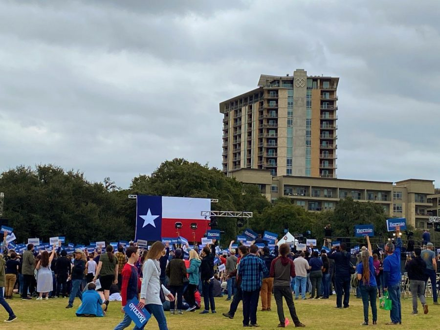 Attendants of the rally gather around a Texas Flag