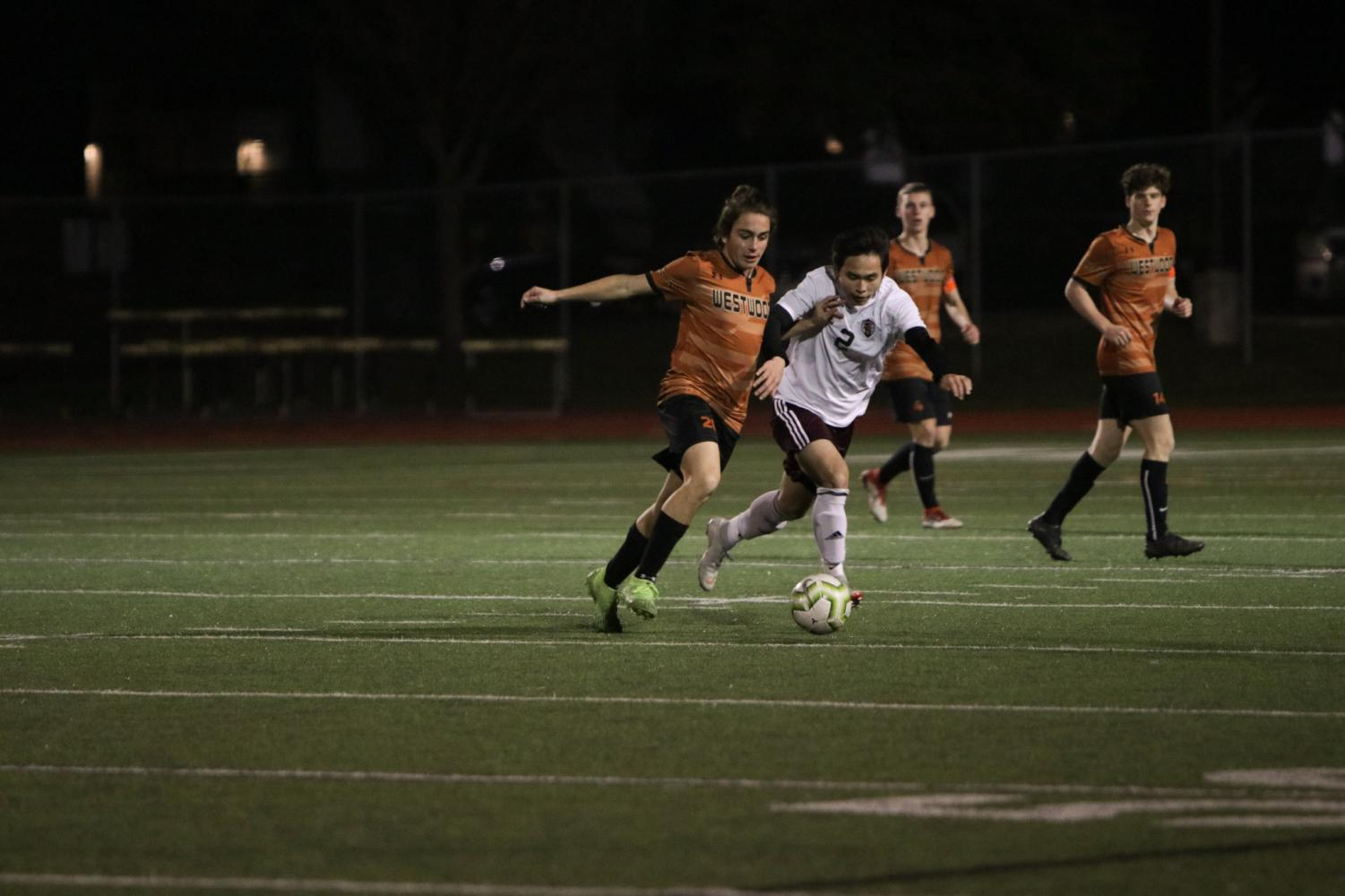 Nikola+Djordjevic+%2721+dribbles+the+ball+downfield%2C+with+an+opponent+close+behind.+This+is+Djordjevic%27s+third+year+playing+for+the+varsity+team.