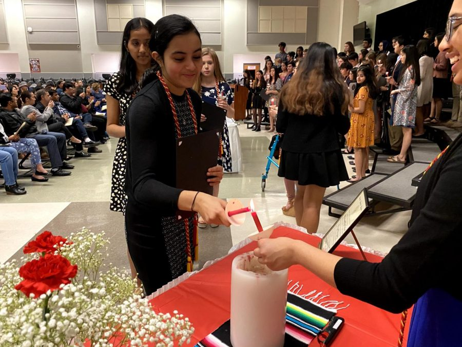 Serena Manwani '22 lights her candle to note her induction to the honor society.