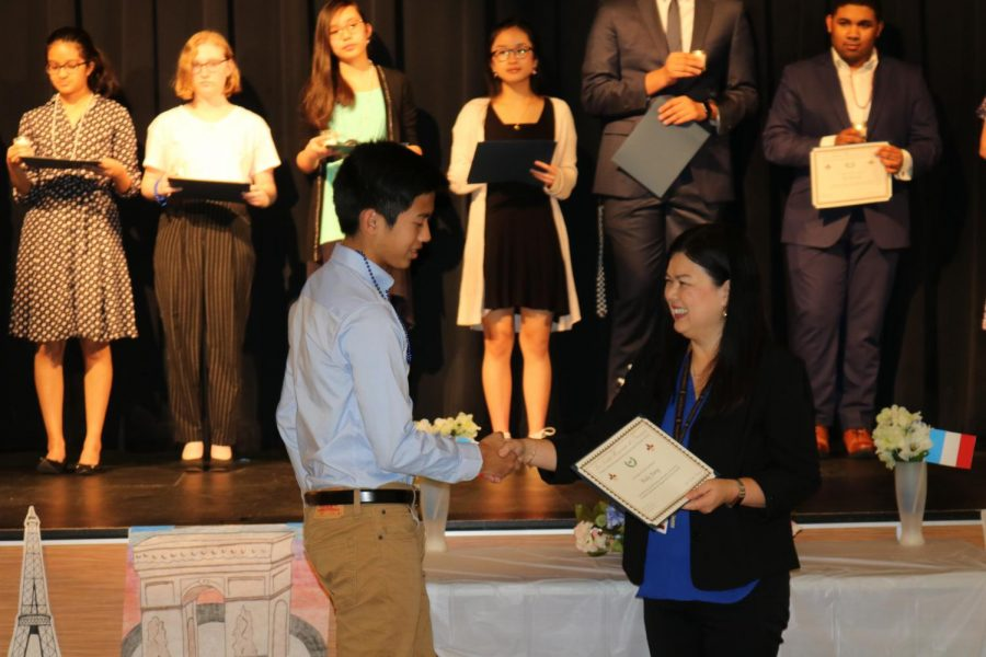 Andie Jiang '23 shakes NFHS Sponsor Mme. Macharia's hand as he recieves his certificate. He then proceeded to line up on the stage with the rest of the new inductees.