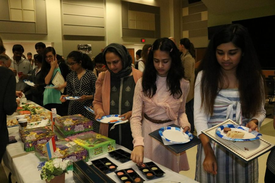 Sophomores Anusha Sajjad and Siri Vangati fill their plates with the wide variety of French foods. From king cakes to macarons, there was plenty of food for the new inductees and their families.