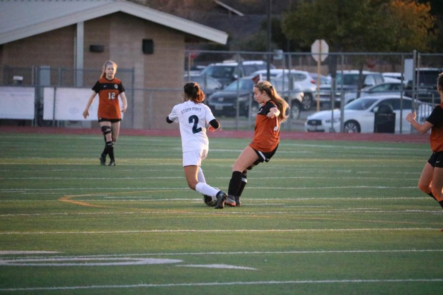 Cate Defendorf '23 tries to get the ball back from a Leander player.
