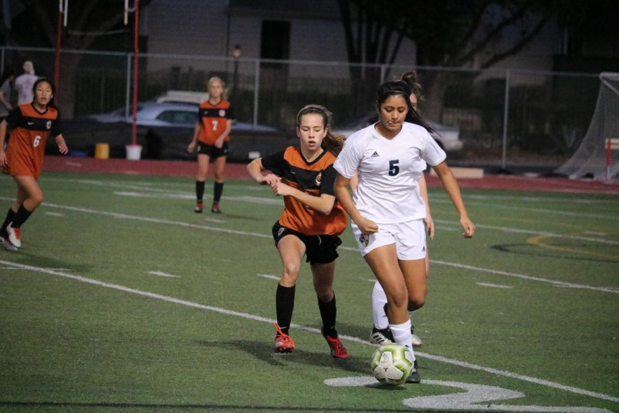 Sasha Brown '23 tries to take the ball away from the Leander player in front of her.