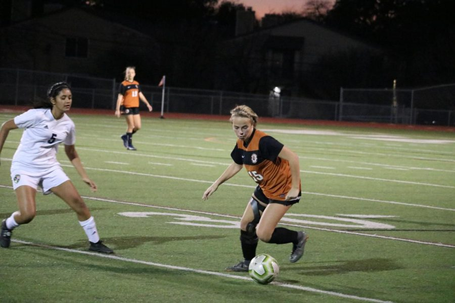 Cate Defendorf '23 dribbles the ball away from the Leander player.