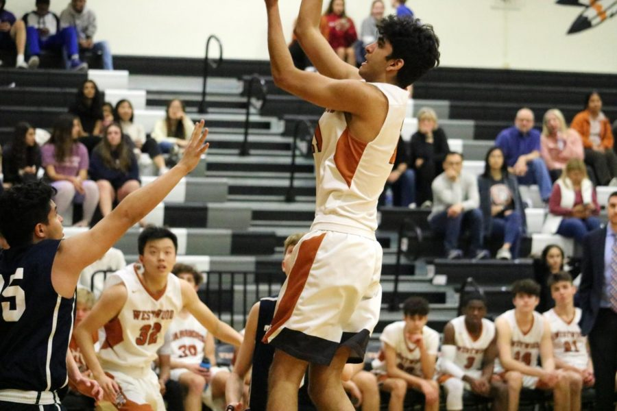 Small forward Vinay Majjiga '22 springs into the air performing a jump shot to score for the Warriors. The Warriors' strong offensive play during the first half of the game kept them at a a three to five point lead.