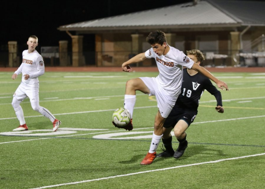 Right in front of a defender, Diego Djordjevic '22 stops the ball with his foot. Djordjevic is one of only four underclassmen on the varsity team.