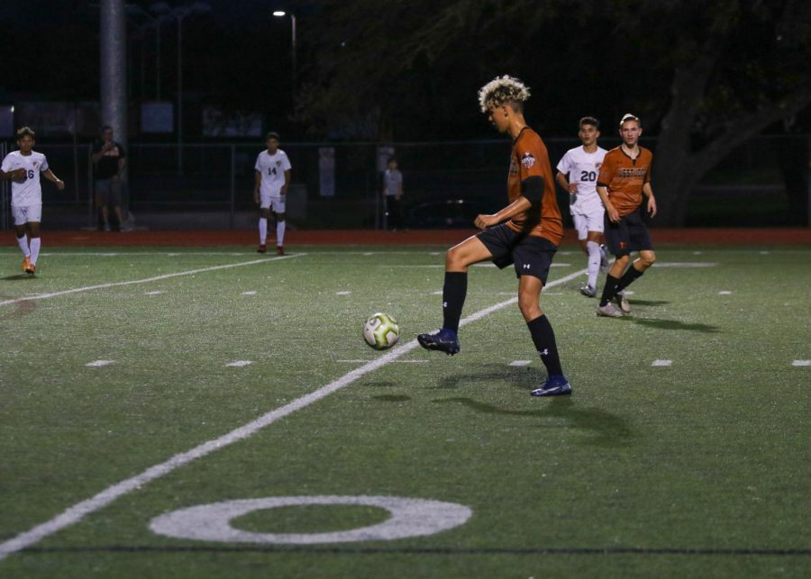 Looking down, Cesar Frias '20 kicks the ball down the field. This was the boys' last home game of the season.