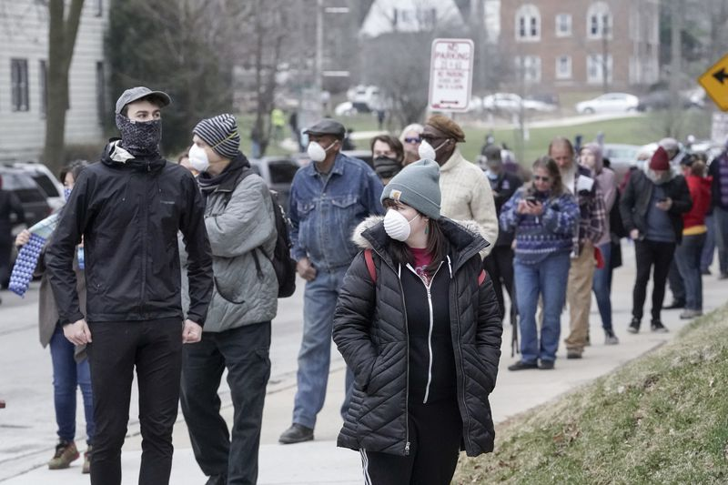 People with protective masks on standing in line to vote.