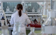 A woman in a lab coat analyzes samples in a laboratory.