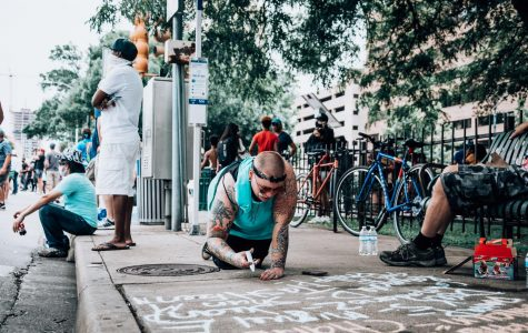 Looking at her phone, a protestor writes a quote with chalk on the streets of downtown Austin. While writing she shared stories of the protests the occurred the previous day with the people around her.