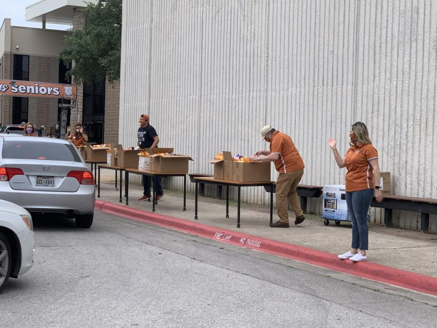 Staff members aid in directing traffic in the drive-through area.