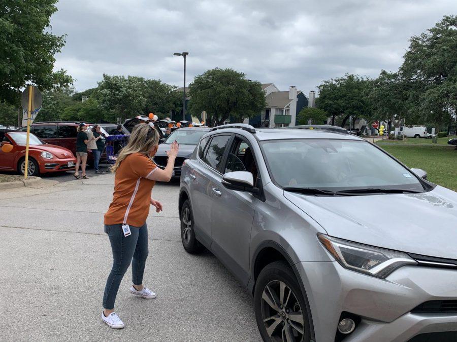 Assistant Principal Jesica Cuellar waves at a senior in their car.